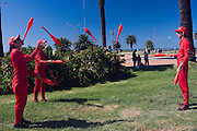 "Montevideo, Uruguay - Jugelers perform next to the beach of the river of Plata in Montevideo. These Jugelers wore red suites for the mobile phone company ""Claro"" and are part of a curret marketing campaign"