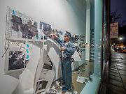 """Portland, Oregon, USA. 26 FEB, 2018. Performance artists mutilate the work of the photographer Robert Frank printed on newsprint in the front window of Blue Sky Gallery in Portland, Oregon, USA. The work was destroyed in a """"Destruction Dance"""" performance defacing the photographs with ink and mutilation with scissors, knives and even ice skates  at the end of it's run. The destruction was Frank's protest regarding today's greed in the global art market."""