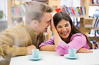Playful young couple with coffee cups on desk in library