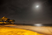 The full moon shines over Makena Beach, located on the Hawaiian island of Maui at night.