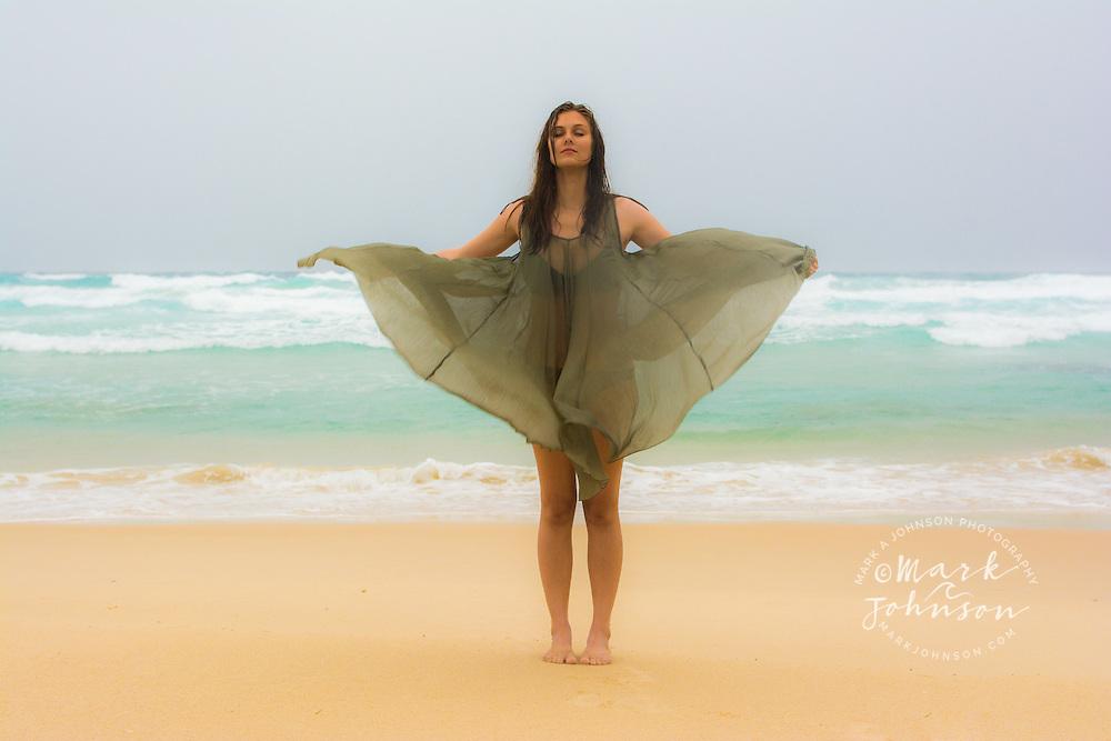 Young woman on the beach on a stormy day, N. Stradbroke Island, Queensland, Australia