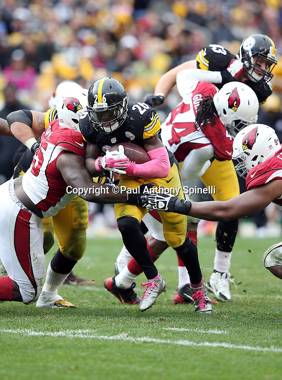Pittsburgh Steelers running back Le'Veon Bell (26) tries to run through two defenders on a 4 yard gain in the Arizona Cardinals red zone during the 2015 NFL week 6 regular season football game against the Arizona Cardinals on Sunday, Oct. 18, 2015 in Pittsburgh. The Steelers won the game 25-13. (©Paul Anthony Spinelli)