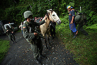 Members of the Jungla, a unit of the Colombian anti-narcotics police, search a man while they are looking for a cocaine lab in a remote part of Cundinamarca state in central Colombia, on June 29, 2007. (Photo/Scott Dalton)