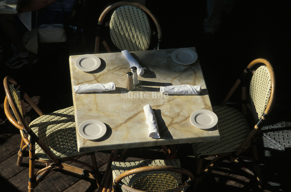 Empty marble table set for four with wicker chairs