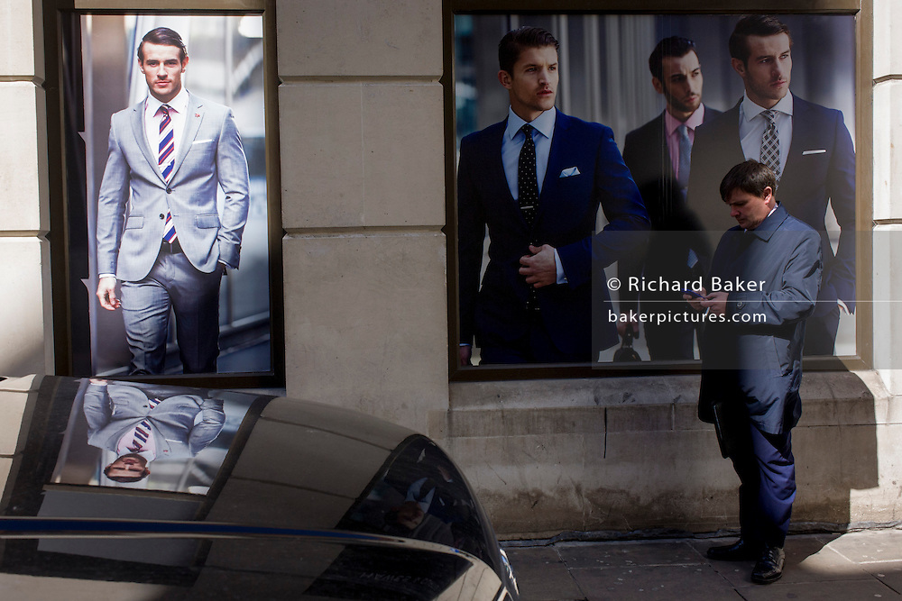 Models on a poster of a stylish clothing shop for businessmen are reflected in the bonnet of a black vehicle parked in the City of London.