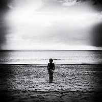 Woman standing alone on beach looking out to sea with grain