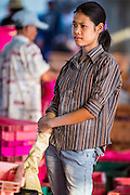 """30 OCTOBER 2012 - PATTANI, PATTANI, THAILAND: An immigrant worker from Myanmar (Burma) in the fishing port of Pattani, province of Pattani, Thailand. The woman has """"thanka' powder on her face, which Burmese use as sunscreen. Thailand's fishing industry relies on immigrant workers, mostly from Myanmar but also Laos and Cambodia. There have been allegations of worker abuse, including charges that workers are held in slave labor like conditions. There are hundreds of thousands of immigrant workers in the Thai fishing industry. Most are from Myanmar (Burma) but there are also Cambodian and Laotian workers in the industry.    PHOTO BY JACK KURTZ"""