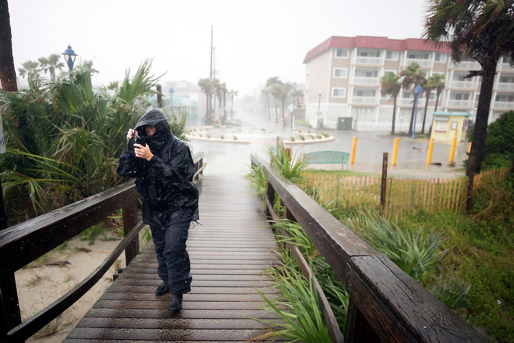 Bethany Kellam reacts to a gust of wind as she walks onto the southend beach of Tybee Island, Ga., Monday, Sept., 11, 2017. Tybee officials said wind gusts are reported at 60 miles per hour on the beach.  (AP Photo/Stephen B. Morton)