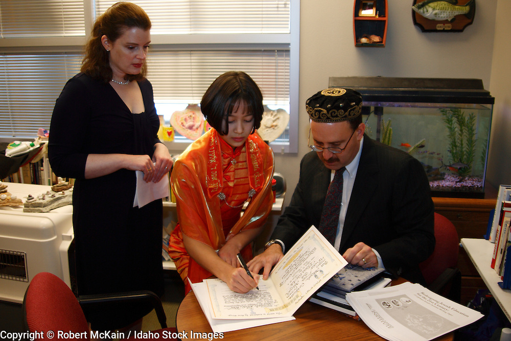 IDAHO. Boise. Rabbi with Asian Jewish girl and her mother signing her Bat Mitzvah certificate. December 2008. #pa080665 MR