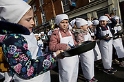 UNITED KINGDOM, Olney: 25 February 2020 <br /> The world's oldest pancake race takes place in the small market town of Olney, Buckinghamshire. It is said to have originated in 1445 when, according to tradition, a woman of Olney ran to the church after hearing the shriving bell, still dressed in her apron  and still clutching her frying pan. <br /> Pictured: Ready for the children's race.