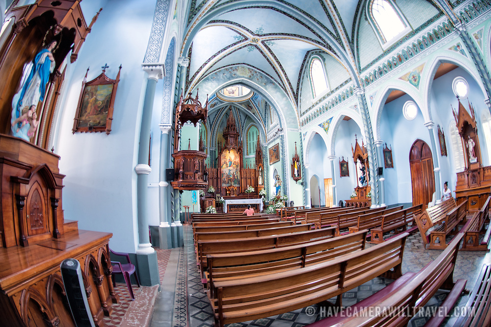 La Capilla Maria Auxiliadora is located in the western part of Granada and features a lavishly decorated interior with walls in pastel blue and green.