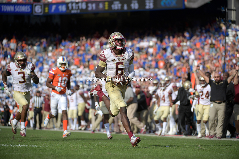 Florida State linebacker Matthew Thomas (6) runs after intercepting a pass intended for Florida tight end DeAndre Goolsby during the second half of an NCAA college football game Saturday, Nov. 25, 2017, in Gainesville, Fla. FSU won 38-22. (Photo by Phelan M. Ebenhack)
