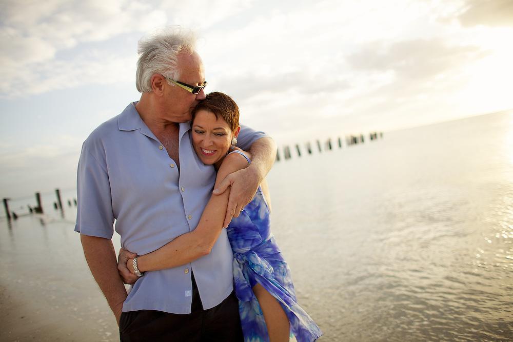 Seniors who found love later in life walk along Naples Beach, Florida.