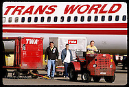 Man drives 'tug' & luggage cart away from TWA jetliner at Lambert International Airport; St. Louis Missouri