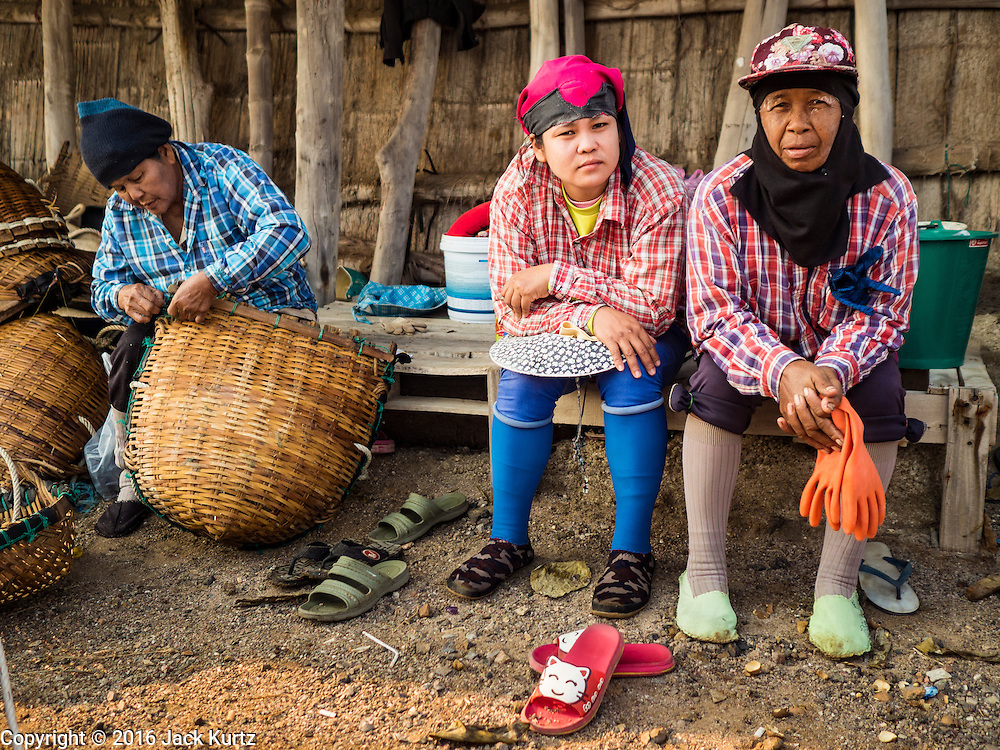 10 FEBRUARY 2016 - BAN LAEM, PHETCHABURI, THAILAND:  Women relax before going out to harvest salt at the beginning of the harvest in Phetchaburi province, Thailand. The salt harvest in Thailand usually starts in February and continues through May. Salt is harvested in many of the provinces along the coast, but the salt fields in Phetchaburi province are considered the most productive. The salt fields are flooded with sea water, which evaporates off leaving salt behind. Salt production relies on dry weather and producers are hoping the current drought will mean a longer harvest season for them.     PHOTO BY JACK KURTZ