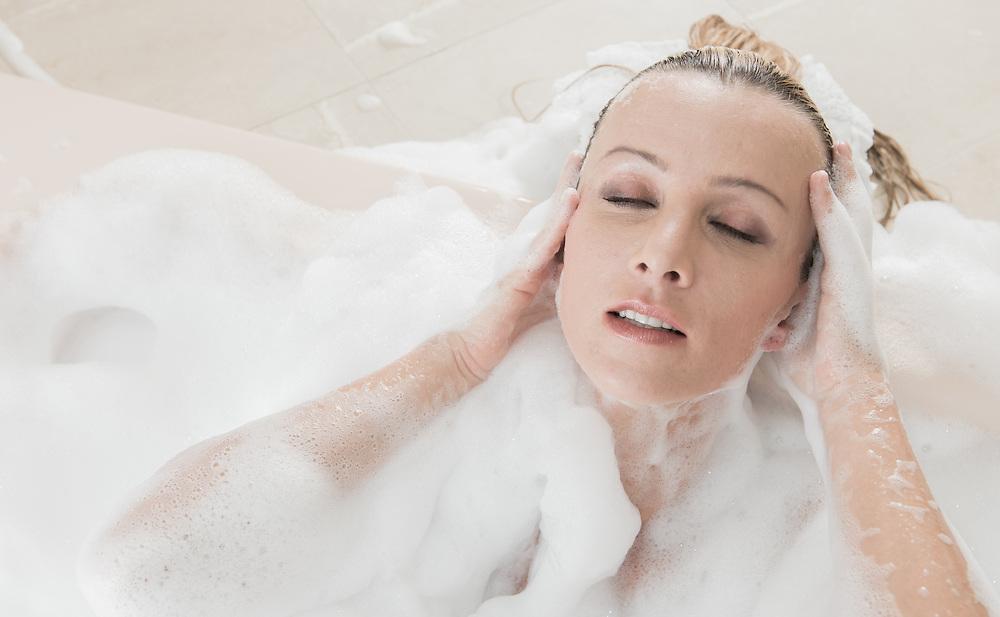 Young caucasian woman in bathtub relaxing