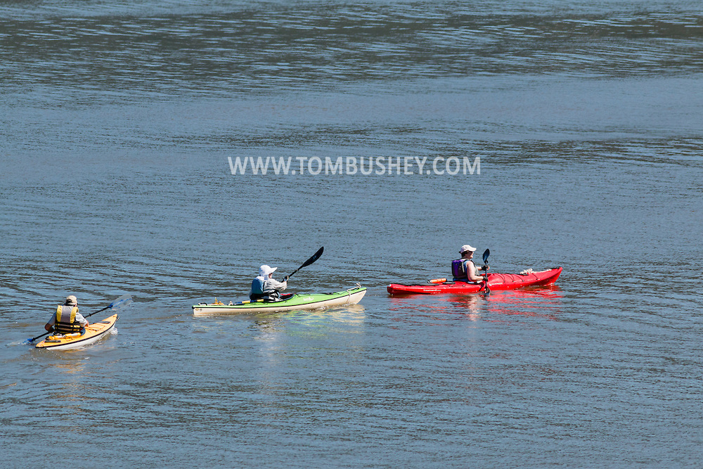 New Windsor, New York - Three people in kayaks paddle south on Hudson River as seen from Plum Point on July 31, 2015.