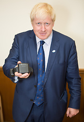 Image ©Licensed to i-Images Picture Agency. 31/07/2014. Croydon, United Kingdom. Mayor of London Boris Johnson holds the UK's first compulsory sobriety 'tag' that measures levels of Alcohol in body for drinkers for residents in Lambeth, Southwark, Croydon or Sutton. Croydon Magistrates' Court. Picture by Daniel Leal-Olivas / i-Images