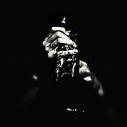 Dramatic light falling on hands of trumpet player with minimal detail of instrument cropped to square format against a black background.