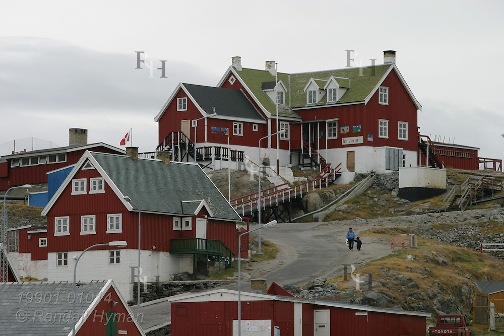 Colorful red and white buildings sit on rocky hill in the island town of Uummannaq, Greenland.