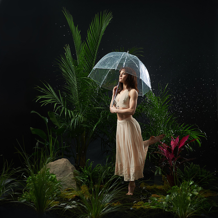 Contemporary dancer in a forest set with ferns and other plants, standing under an umbrella with rain drops falling overhead. Photographed by Rachel Neville in New York City.