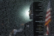 U.S. President Barack Obama's shadow is reflected on the Vietnam Veterans Memorial wall, etched with the names of U.S. military members who died during the war, as he delivers remarks during an observance of the 50th anniversary of the Vietnam War, on the National Mall in Washington, May 28, 2012.