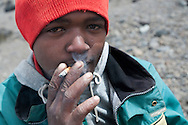 Despite the altitude of over 15,000 feet, a porter relaxes wth a cigarette after putting down his load of up to 20kg. Many porters smoke on the trails of Kilimanjaro, despite the thin air and exhausting work they must complete on a daily basis.