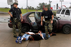 24th Sept, 2005. Beaumont, Texas. USA..Hurricane Rita. Police from the Beaumont rapid reaction force arrest looters who they captured breaking into a Chevron petrol station just off interstate 10..Photo; Charlie Varley