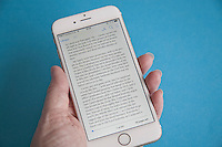 Reading an ebook on a Gold and white Apple iPhone 6 againdt a blue background