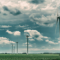 A row of large wind turbines in the countryside under a summer sky with white clouds