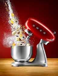 Dynamic image of some cake ingredients being thrown into a bowl of an iconic SMEG Mixer.
