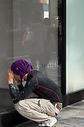 A construction worker surveys a shop front display area.