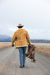 cowboy walking down a dirt road with a saddle