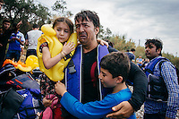 A father and his kids hug each other after the boat safely arrives at a northern shore of Lesvos island in Greece, Aug 15th, 2015.