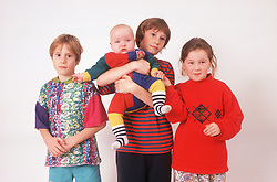 Portrait of group of young children with baby,