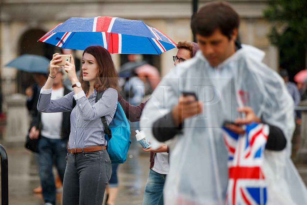 © Licensed to London News Pictures. 27/06/2017. London, UK. Tourists take shelter from the rain in Trafalgar Square, London on Tuesday, 27 June 2017. Photo credit: Tolga Akmen/LNP