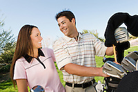 Golfing Couple Grabbing Clubs