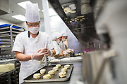 Head Chef Ray Kim of South Korea prepares raisin pastries during the Grand Opening Ribbon Cutting Ceremony at Paris Baguette Cafe in Milpitas, California, on May 16, 2014. (Stan Olszewski/SOSKIphoto)