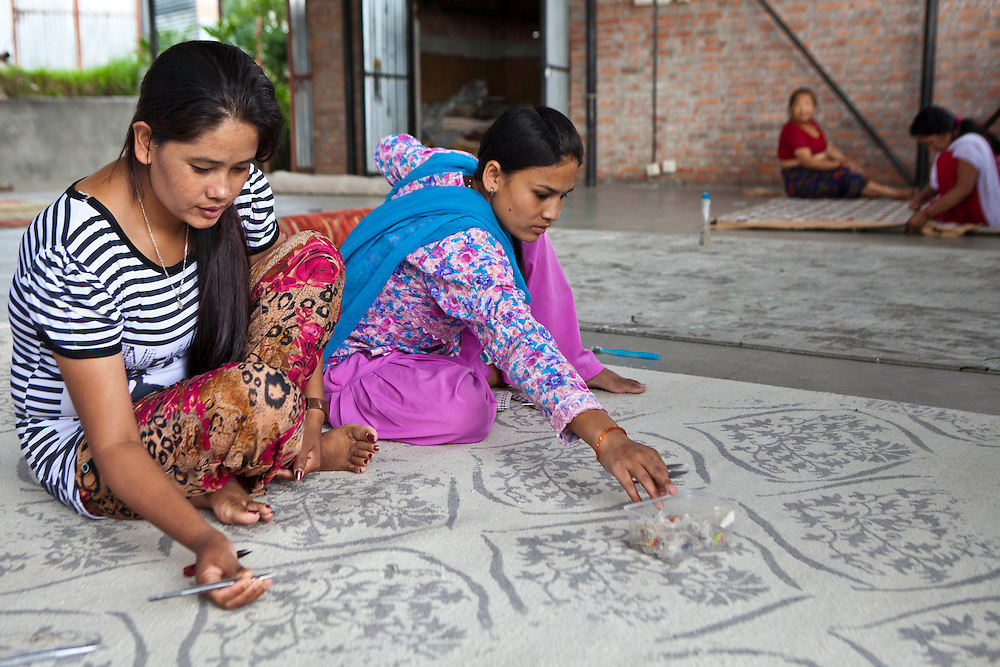 Two female Nepalese factory workers pull threads though the weave to make rugs and carpets.  They work in a semi-sheltered outdoor area of the R.C Rug Factory based in the Narayanthan area of Kathmandu, Nepal.