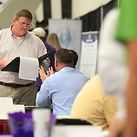 John Parker, of Tupelo, talks with Randy Futral, owner of ACR Coaches, about job openings for drivers during the Mega Job Fair held Tuesday in Building V of the Tupelo Furniture Market.