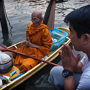 Thai Buddhist monk Luang Pho Malai, 91 years old, is seen Saturday, June 29, 2013, as he accepts offerings along a river canal near his pagoda on the outskirts of Bangkok.   For the past 30 years Luang Pho Malai has made his daily round to attend to the faithful in a small wooden boat to collect their offers and dispense blessings.  While many of Bangkok's major canals were filled in and paved over during the building boom of the 1980's klong Thavi Watthana still serves the needs of a impoverished community.