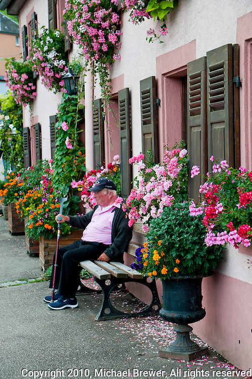 An old man sitting on a bench amongst the flowers in Obrey, Alsace, France.