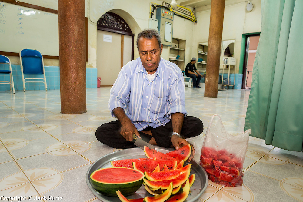 26 JULY 2013 - BANGKOK, THAILAND:  A Muslim man cuts up watermelon for desert for the Iftar meal at Haroon Mosque in Bangkok. Iftar is the Muslim meal that breaks the day long fast during Ramadan. Ramadan is the ninth month of the Islamic calendar, and the month in which Muslims believe the Quran was revealed. The month is spent by Muslims fasting during the daylight hours from dawn to sunset. Fasting during the month of Ramadan is one of the Five Pillars of Islam. Muslims believe that the Quran was sent down during this month, thus being prepared for gradual revelation by Jibraeel (Gabriel) to the prophet Muhammad.    PHOTO BY JACK KURTZ