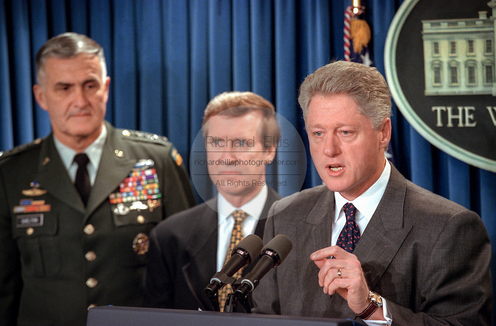 US President Bill Clinton makes a statement in the Briefing Room of the White House November 15, 1998 in Washington, DC. Clinton announced that he called off airstrikes on Iraq after Saddam Hussein agreed to allow the UN to resume weapon inspections. Standing with Clinton are Secretary of Defense William Cohen and Chairman of the Joint Chiefs General Hugh Shelton.