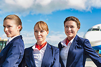 Portrait of three young attractive flight attendants standing against airplane in airport