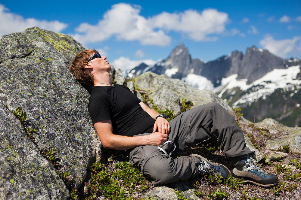 Ian Derrington takes a nap on Damnation Peak with the distinctive summit of Mount Triumph in the distance, North Cascades National Park, Washington.