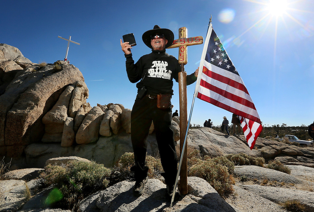 Jim, no last name given, displays his bible during an unveiling ceremony for the Mojave Cross on Veterans Day in Cima, California on Sunday, November 11, 2012.  A battle has been brewing for over Thirteen years over whether the cross can legally stay on Sunrise Rock because it violates Separation of Church and State and is in the Mojave National Perserve which is on Federal Lands.  The Veterans of Foreign Wars and American Legion Society raised money to purchase the plot of land and has kept the cross in place and today serves as war memorial.(Photo by Sandy Huffaker)