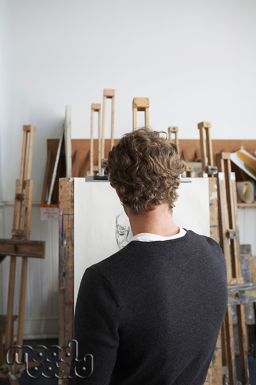 Artist drawing charcoal portrait in studio back view
