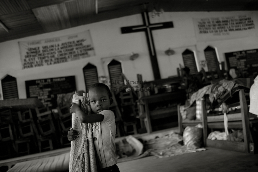 a small boy holding his sleeping carpet  in  The Christian church in Boali, some km. outside Bangui are now working as temporary shelter for Muslim refugees who have been forced to leave their home due to attacking Anti Balaka militias.-- Sadly there is nothing new about the atrocities being inflicted against civilians in the Central African Republic. What is new is the scale of the violence and widespread and arbitrary targeting of people solely because of their religion.<br /> Christian militia loyal to former President Francois Bozize began an offensive last week against the capital, Bangui. The militia attacked mosques, daubing walls with the slogan &quot;Tuer les musulmans&quot; (Kill the Muslims) in what Amnesty International describes as &quot;a shocking escalation of anti-Muslim rhetoric within the Christian community.&quot;<br /> In turn, largely Muslim militia known as the Seleka have killed Christians in their homes and attacked hospitals and churches. Tens of thousands of Christians have taken refuge in churches and Roman Catholic missions around the country. Some are taking shelter in hangars at the Bangui airport. One missionary in Bangui told a Roman Catholic charity: &quot;We have never seen anything as bad as this before. We're at the mercy of God, please pray for us.&quot;<br /> French troops are trying to disarm rival groups of vigilantes before a Rwanda-style genocide can take hold. But the Central African Republic is the size of France, and there are fewer than 2,000 of these troops currently deployed -- along with some 2,500 African peacekeepers. The French intervention has reduced the violence in Bangui, but the long-term danger is that sectarian brutality will perpetuate communal hatred.