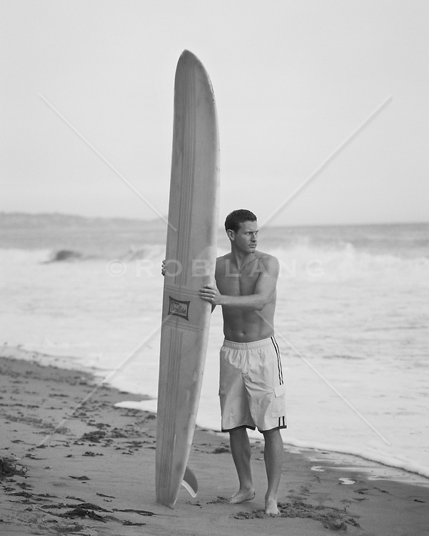 Man holding a long board at the beach in Malibu